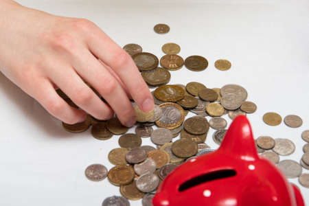 many coins of different countries lie on the table near the red piggy bank. Financial concept.