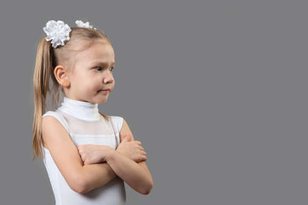 Portrait of a beautiful caucasian little displeased girl arms folded, closed pose. The idea of child discontent on the actions of adults. Place for text, copyspace. Banco de Imagens