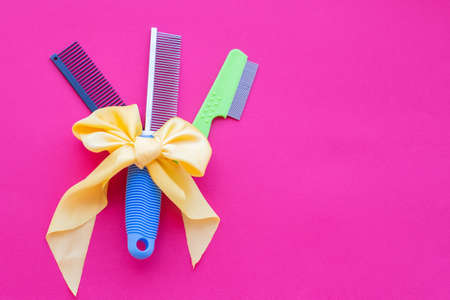 Three types of hairdressing scissors with a yellow bow on a pink background. Top view, layout, copy space.
