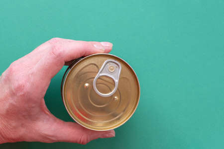 The hand of an adult man holds a closed can of canned food with a public key on a green background. Top view of tin can with ring pull isolated on green background with copy space. Close-up 免版税图像