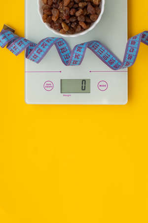 Dietary sweets without sugar, centimeter tape, scales on a yellow wooden background. The concept of a healthy diet, weight control. Losing weight. View from above