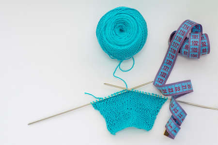 Top view of a knitted pattern on a knitting needle made of blue yarn, a centimeter tape on an isolated background, copy space. Needlework concept, handmade, homemade. Imagens - 147733206