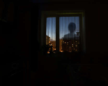 Shadow silhouette of a man in the night window, dark background, copy space. The idea of danger, loneliness, someone spying Фото со стока