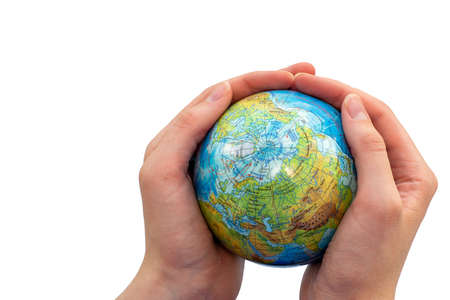 Close-up hands of a young woman holding a globe. The concept of care, protection.