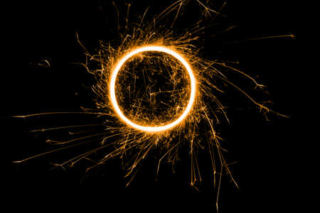 Happy New Year, festive, colored sparkling circle from a burning sparkler on a black background. Holiday concept, background, copy space. Standard-Bild