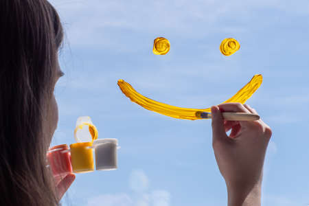 Close-up of a girl draws a yellow smile on glass against a blue sky. The concept of joy, positive, happiness.