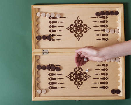 A hand throws a white bone over a backgammon board. Victory concept.