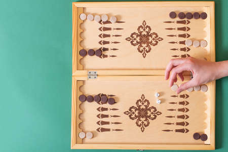 Hand holds a white chip for the next move, a game of backgammon. Victory concept. Stock Photo