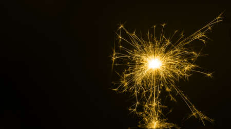 Happy New Year, colored sparkling burning sparkler or salute on a black background. Holiday concept, background, copy space.
