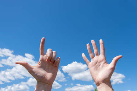 Gesture closeup of a womans hand showing one open palm and two fingers up isolated on a blue sky background