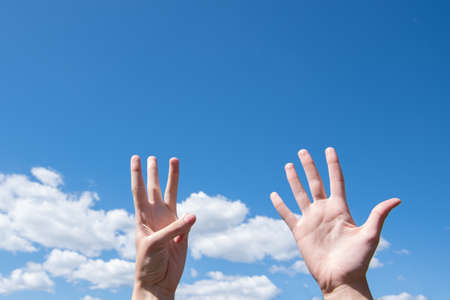 Showing a closeup of a womans hand showing one opened palm and three fingers up isolated on a blue sky background Banco de Imagens