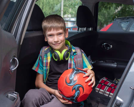 Portrait of a happy boy getting out of the car with a red ball in his hands and with a school bag. The boy was brought to school by car. Concept for back to school, education, soccer