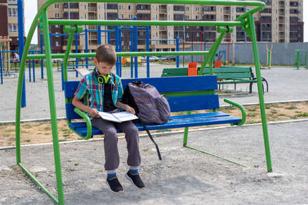 A portrait of a disgruntled, unhappy boy who is forced to study. A child in the yard sits on a swing and reads a book or a notebook, a schoolbag. Education concept, summer vacation, back to school