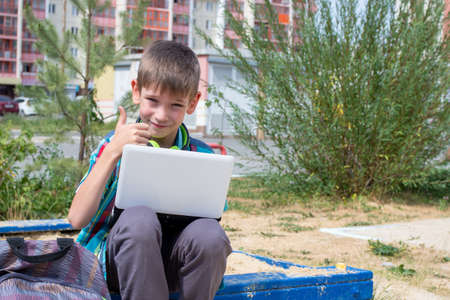 Portrait of a happy boy, holding a laptop, raised his thumb up. The boy likes to study on a laptop, do homework in the yard. Education concept, summer vacation, back to school