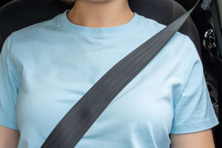 Close-up of woman fastening seat belt in car. Front view. Car safety concept.
