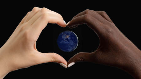 Black and white heart shaped hands with planet Earth: America in the dark.