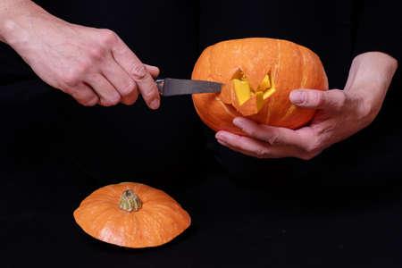 Step 3 Cutting eyes and mouth in a pumpkin with a knife to prepare Jack's lantern, isolated on black background, close-up, copy space. Step-by-step instructions for making Jack's lantern