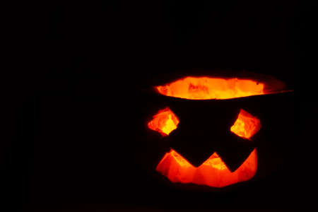 Halloween pumpkin smile and scary eyes for a party, Jack Lantern isolated on black background.