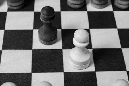 The first move in chess was made by pawns to meet each other. Chess game start, close-up, selective focus black and white. Business concept start of business negotiations, business cooperation 版權商用圖片