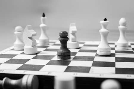 One black pawn stands against a whole board of white chess pieces, selective focus, copy space. The concept is one against all. Leadership concept among competitors