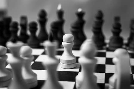 The first move in chess was made by a white pawn. Chess start, close-up, selective focus, black and white. Business concept start of business negotiations, business cooperation