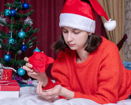 A sad girl in a red Christmas hat and sweater pours coins from a piggy bank in a home interior decorated for Christmas. Money saving concept Stock Photo