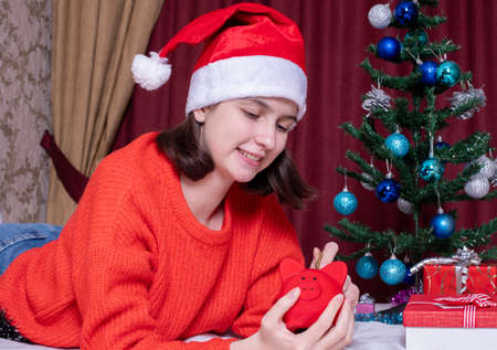 Smiling teenage girl in a Christmas hat and red sweater takes out coins from a red piggy bank for shopping Christmas gifts. Online shopping concept, christmas fair