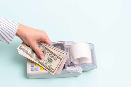 Online shopping concept. Close-up of a female hand holding several hundred dollar bills above the cash register to pay for a product or service on a blue background, top view, copy space.