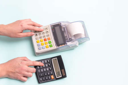 Close-up of a female hand pressing a finger on a cash register button and a hand pressing a button on a calculator on a blue background, top view, copy space. Counting on the product cost calculator Stok Fotoğraf