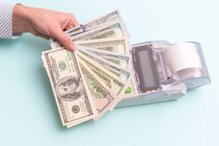 Business concept. Close-up of a female hand holding several hundred dollar bills above the cash register to pay for a product or service on a blue background, top view, copy space.