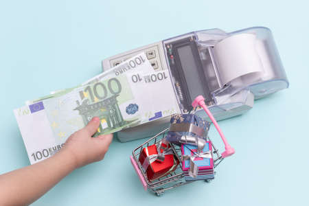 Close-up of a child's hand holding a copy of 100 euro banknotes above the cash register for buying boxes of gifts in a trolley on a blue background, top view, copy space. Online shopping concept.