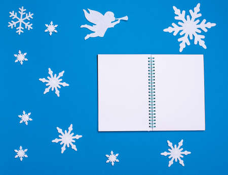Christmas and new year flat composition with white blank notepad, white angel playing trumpet and christmas snowflakes on blue background, copy space