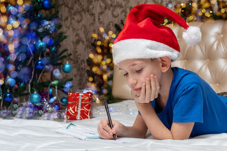 New Year and Christmas traditions. A little Caucasian boy in a red Santa hat writing a letter to Santa at home decorated for Christmas. A child is waiting for a gift from Santa Imagens