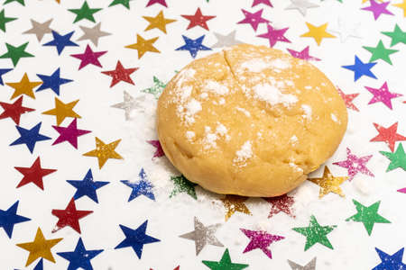 Raw dough for bread or pizza on a background of colorful stars, close-up, top view. Making homemade baking dough. Homemade baked goods