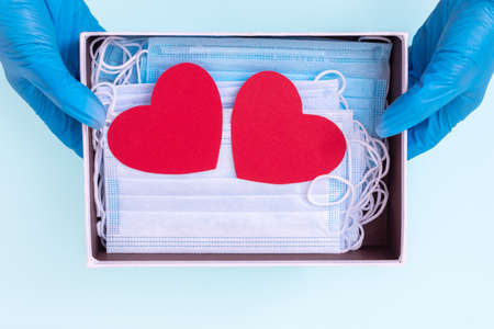 Hands in blue medical gloves hold an open gift box with protective medical masks and two red heart shapes. Safe gifts concept. Actual gift for Valentine's Day during the coronavirus period