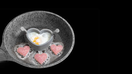 Cooking delicious breakfast with scrambled eggs and sausages in the shape of a heart in a gray frying pan isolated on black background, banner, copy space, top view. Valentines Day Cooking