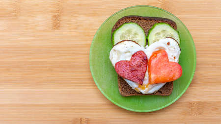 Cucumber sandwich, heart shaped scrambled eggs with sausages and heart shaped tomato on a green plate on a bamboo background, top view, copy space. Breakfast for loved ones on Valentines Day 版權商用圖片