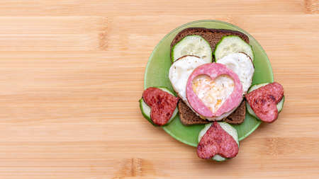 Sandwich with heart shaped fried eggs, sausages and cucumbers on a green plate on a wooden background, top view, copy space. Breakfast for loved ones on Valentines Day