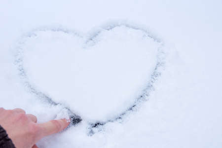 Female hand is drawing a heart shaped love symbol on the texture of white snow, close-up, copy space. A manifestation of love in the form of a heart. Valentines Day concept 版權商用圖片