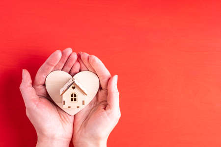 Two hands hold a wooden heart shape and a wooden house symbol of family, love, relationships on a bright red background with copy space, close-up. Valentines Day gift