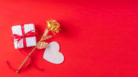 Wooden heart shape, a gift in white paper and a red ribbon and a yellow gold rose symbol of love, family relationships, on a bright red background, copy space, banner, top view. Valentines Day gift