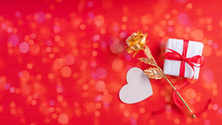Wooden heart shape, a gift in white paper and a red ribbon and a yellow gold rose symbol of love, family relationships, on a bright red background with bokeh, copy space, banner. Valentines Day gift
