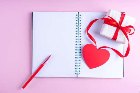 White blank open notepad, red pen, gift box with red ribbon and pink paper heart shape on pink background, copy space, flat lay, top view. Valentines day background. Writing romantic letters. 版權商用圖片