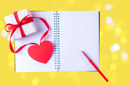 White blank open notebook, red pen, gift box with red ribbon and pink paper heart shape on yellow Illuminating 2021 background with bokeh, copy space, flat lay, top view. Valentines day background
