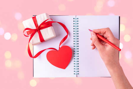 Female hand writes a love message with a red pen in a white blank open notebook, next to a gift box with a red ribbon and a red heart on a pink background with bokeh. Happy Valentines Day