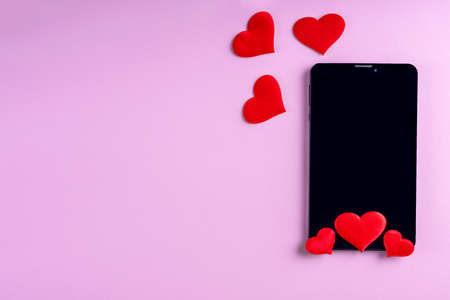 Black blank phone screen with red heart shape on pink background, copy space, minimalism, flat lay. Valentine day concept. Concept to like in social networks or Dating app 版權商用圖片