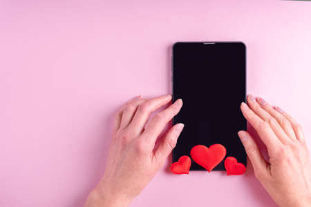 Online shopping concept. Female hands on a black blank tablet screen with red heart shape on a pink background, copy space, minimalism, flat lay. Valentine day concept