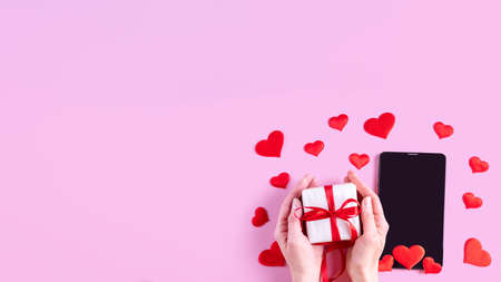 Hands hold a gift with a red ribbon over a black blank screen of a tablet or phone with red heart shape on a pink background, copy space, banner. Postcard for Valentines Day, Mothers Day 版權商用圖片