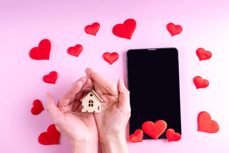 Hands hold a small mock up of a wooden house over a black blank screen of a tablet or phone with red heart shape on a pink background. Greeting card for Valentines Day, Family Day, Mothers Day