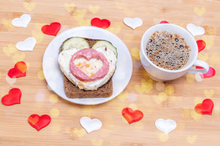 Coffee in a white cup and a sandwich with heart-shaped fried eggs, sausages and cucumbers on a green plate on a wooden background with hearts and bokeh, top view. Valentines Day Breakfast
